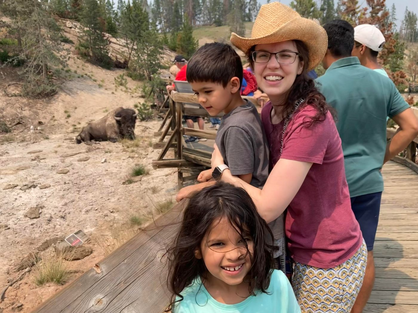 A Mom in a Cowboy hat, standing with her children, a five year old boy and eight year old girl, some distance away from a Buffalo in Yellowstone National Park.